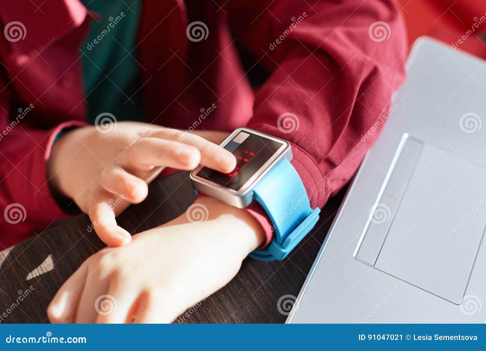 Um close-up das mãos do ` s da criança com relógio esperto Relógio eletrônico tocante Conceito Wearable do dispositivo Mostrando