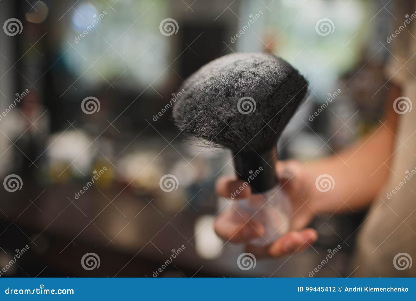 Um close-up de um acessório de rapagem em um fundo borrado Uma escova preta no talco branco Ferramentas para cortar a barba