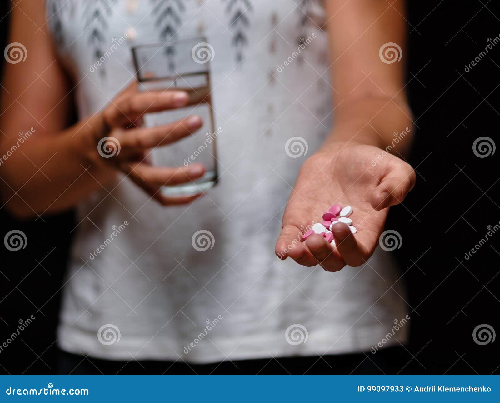 Um close-up disparou do montão dos comprimidos e de um vidro da água nas mãos fêmeas Jovem mulher que guarda tabuletas em um fund