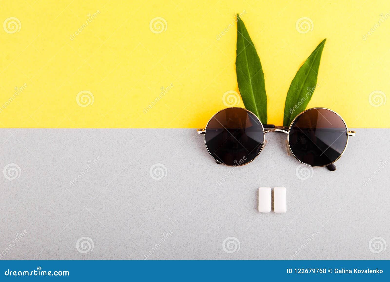 Um coelho feito com vidros, um par de pastilha elástica e verde, folhas prolongadas Conceito mínimo da configuração lisa