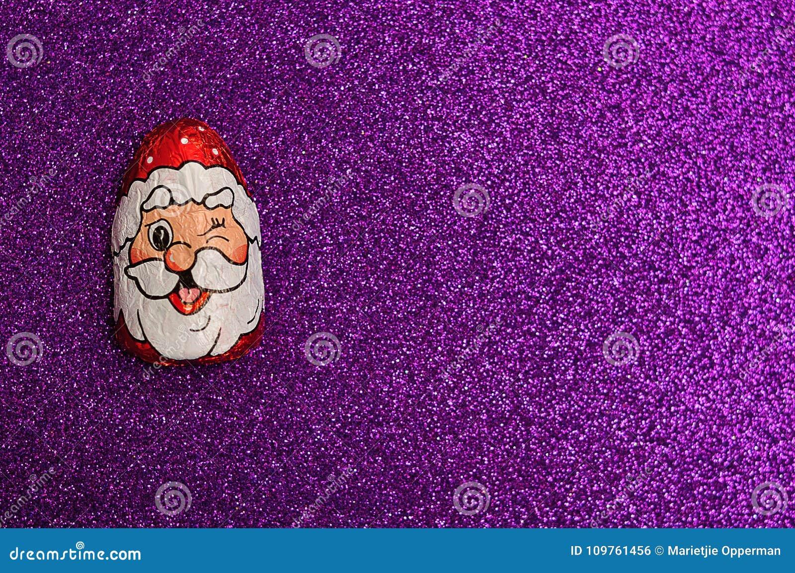 Um com cobertura em chocolate com o envoltório da cara do ` s de Papai Noel