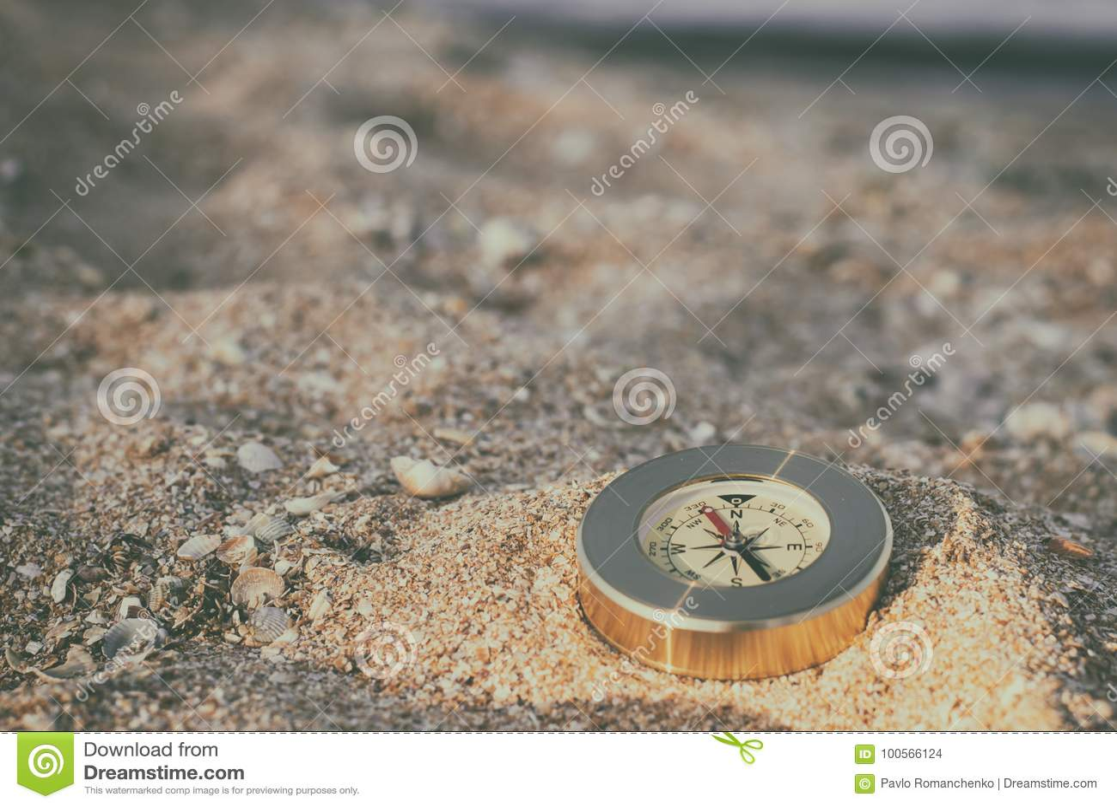 Um compasso que mostra o sentido encontra-se na areia do mar com shell