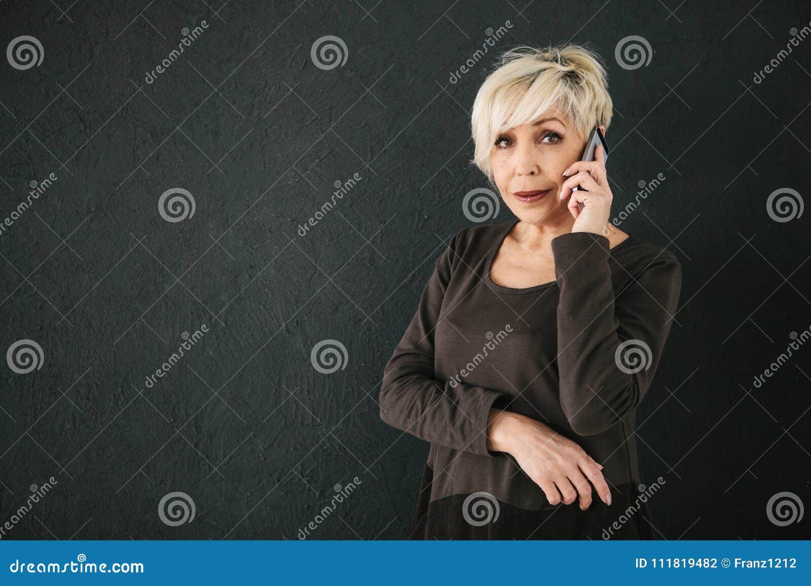 Um consultante fêmea idoso positivo bem sucedido está negociando um telefone celular Uma comunicação entre a utilização dos povos