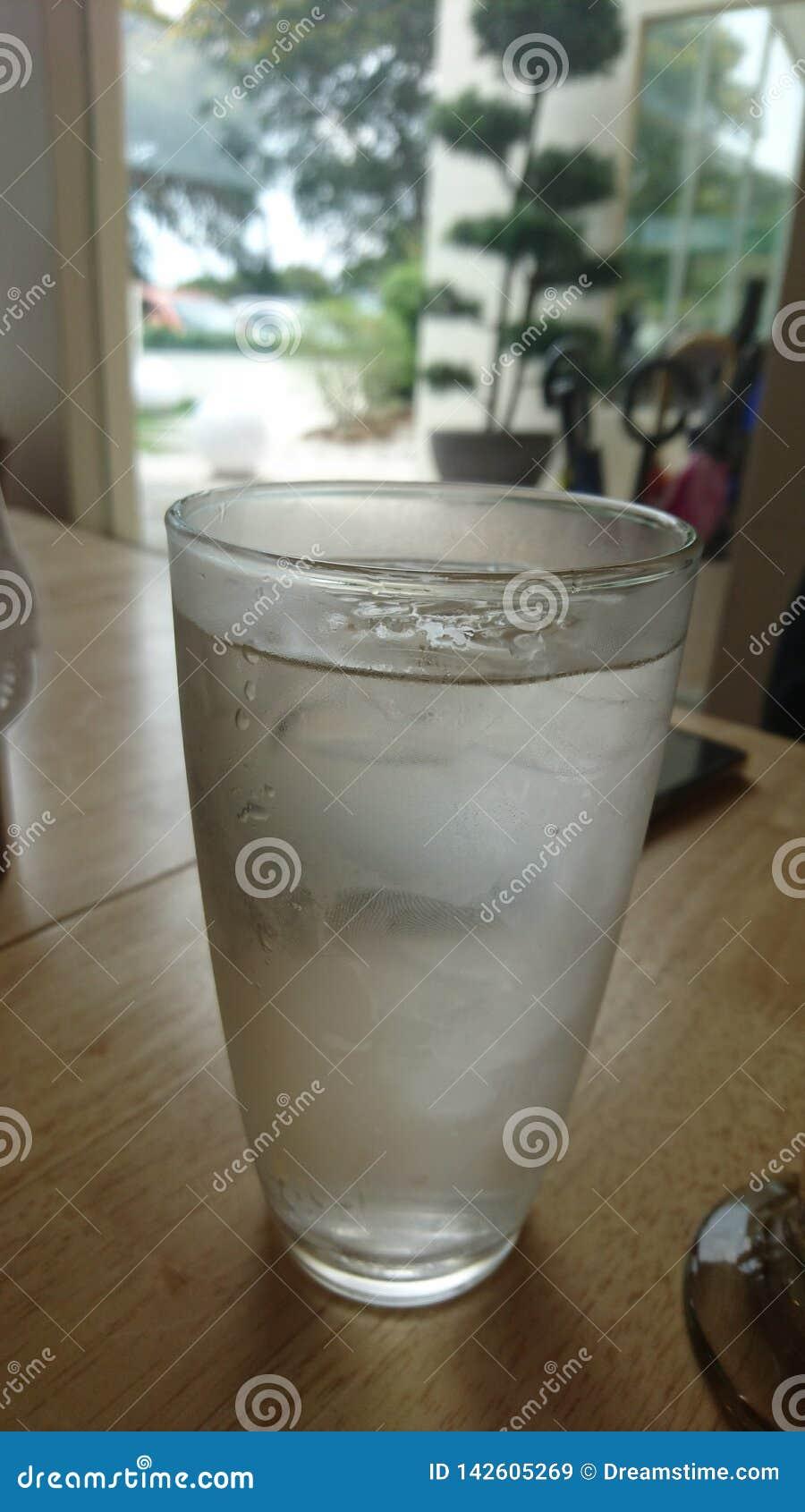 Um copo da água fria a refrigerar
