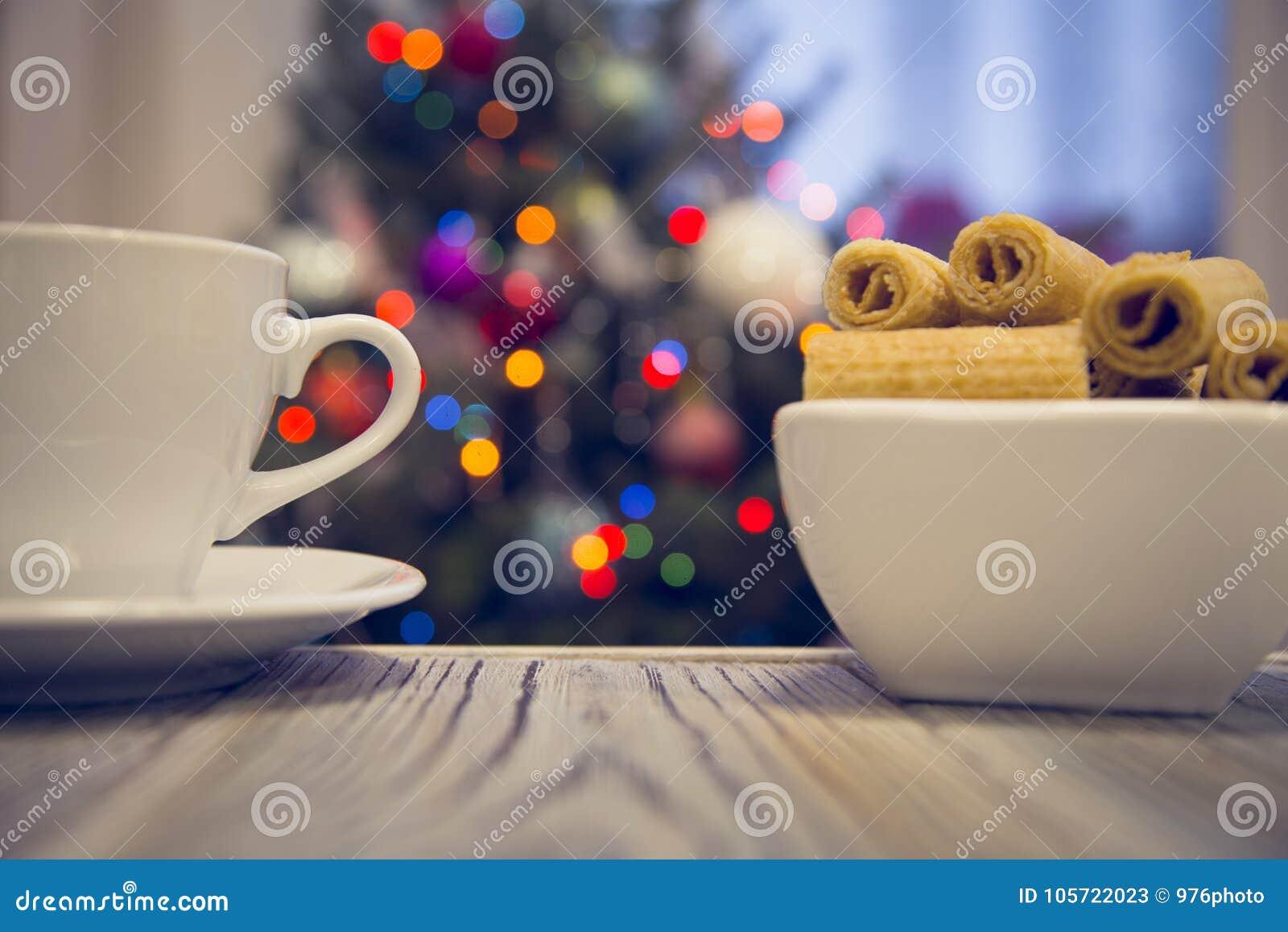 Um copo de chá e uma bacia de cookies em uma tabela de madeira contra a árvore de Natal decorada