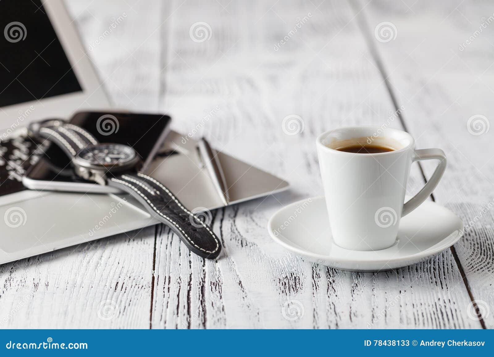 Um copo do café preto e de equipamentos ocasionais do negócio na placa de madeira