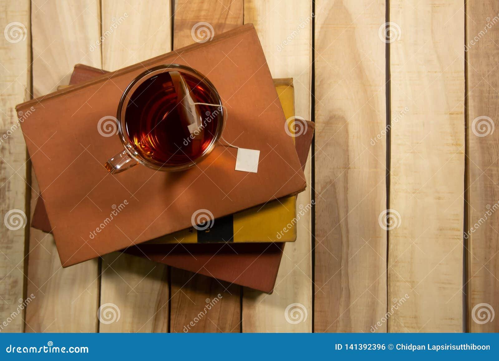 Um copo do chá é ficado situado no livro E grupo em uma composição de tabela de madeira com o espaço da cópia no fundo de madeira