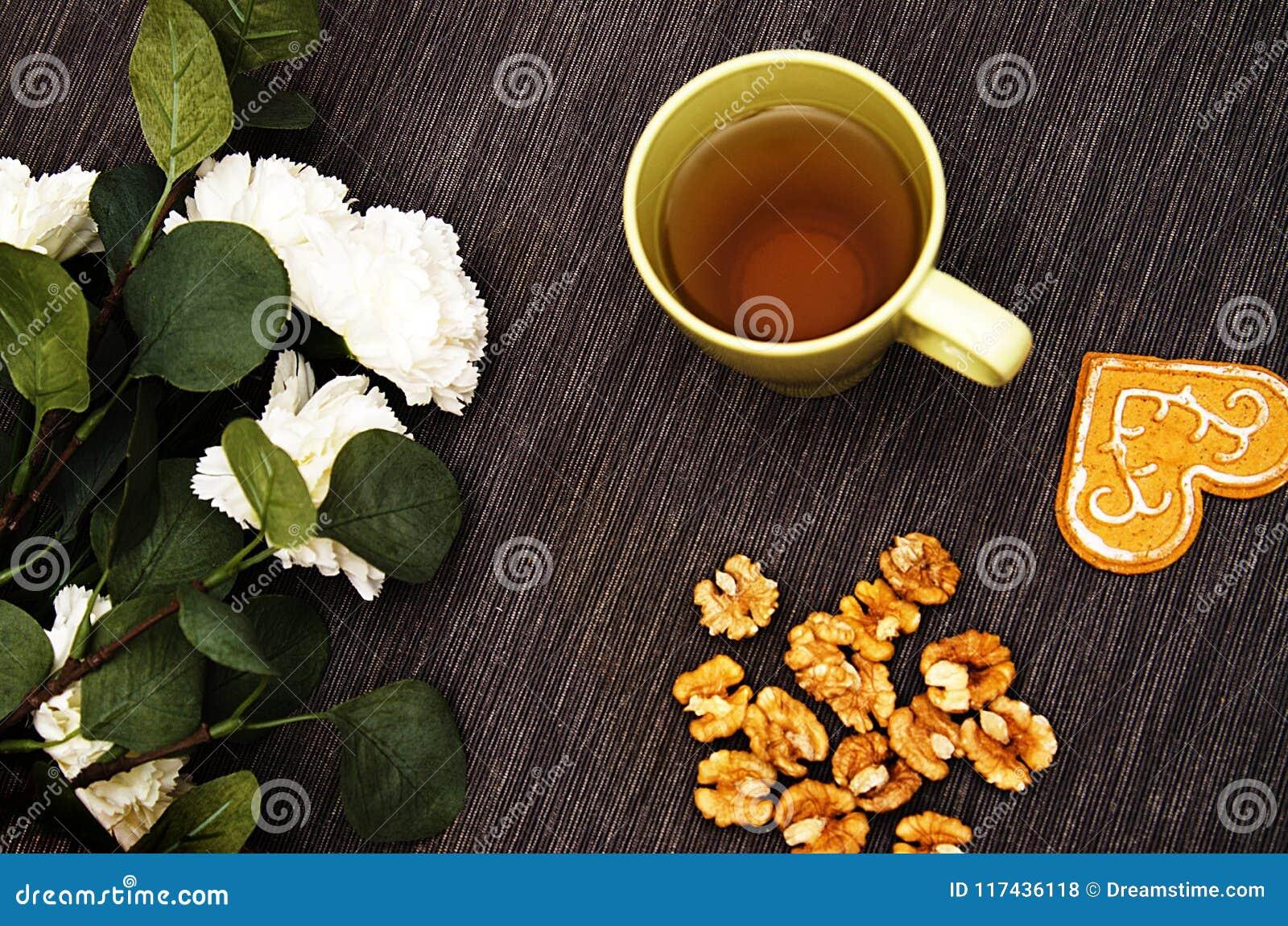 Um copo do chá verde em uma tabela com flores brancas e uma noz em um fundo escuro