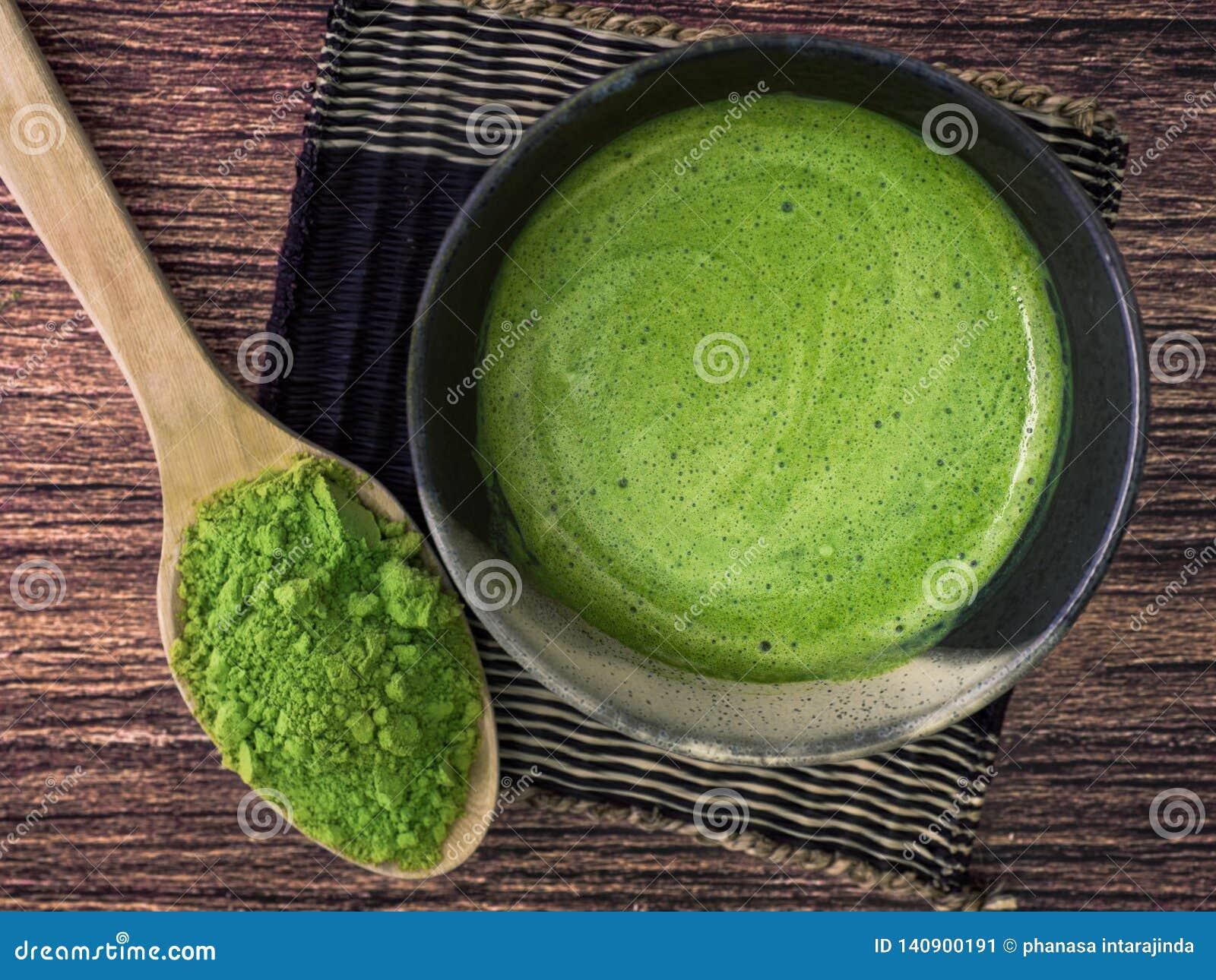 Um copo do latte do chá verde no pó de bambu da esteira e do matcha na colher no fundo de madeira