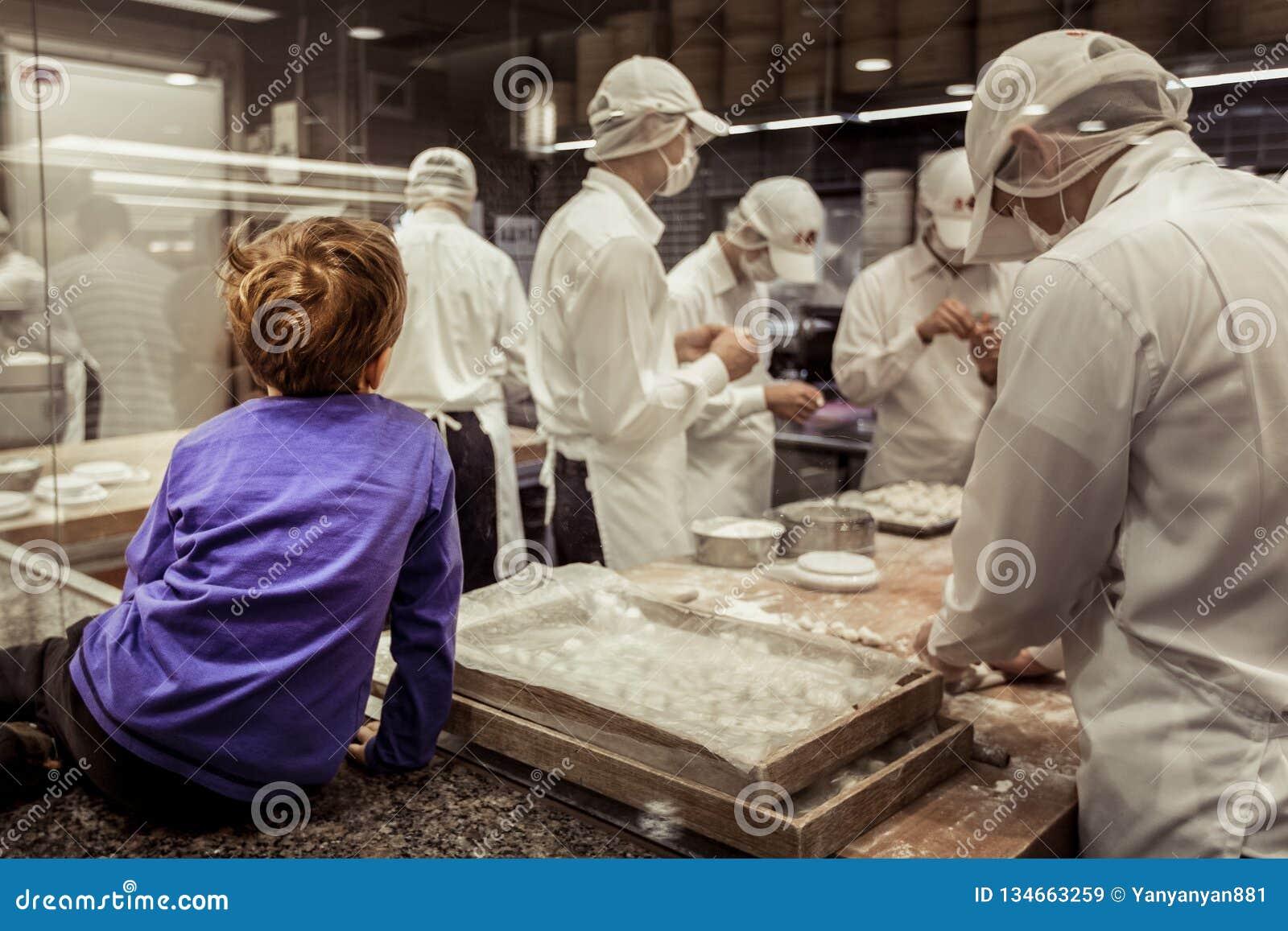 Um cozinheiro chefe de observação da janela nova do menino que faz bolinhas de massa chinesas