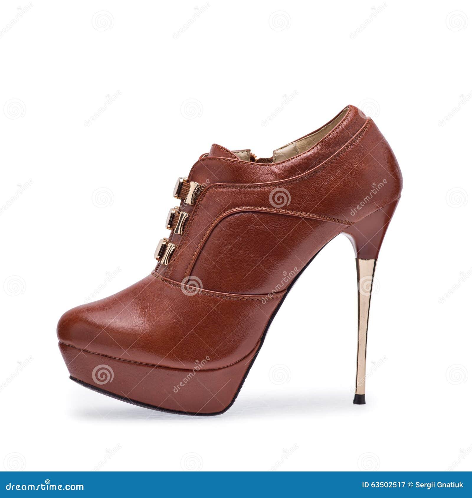 Um de estiletes marrons das sapatas das mulheres com uma correia decorativa