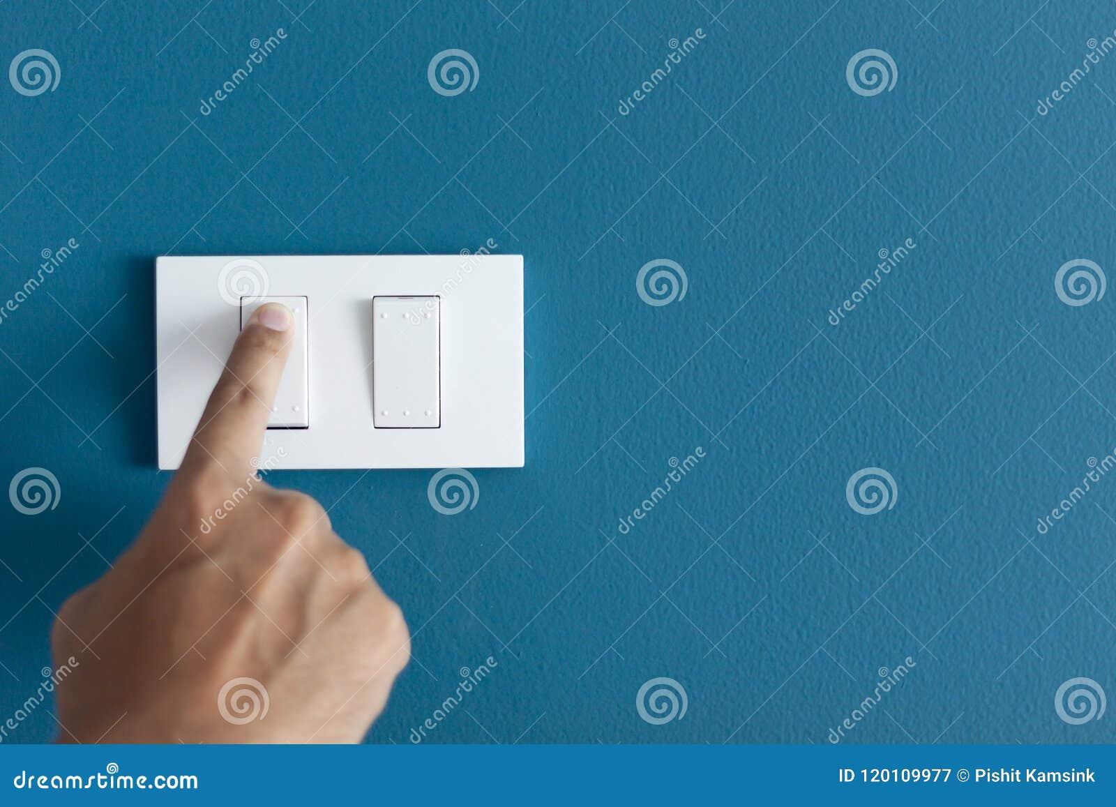 Um dedo que gira sobre o interruptor de iluminação em áspero na parede escura azul