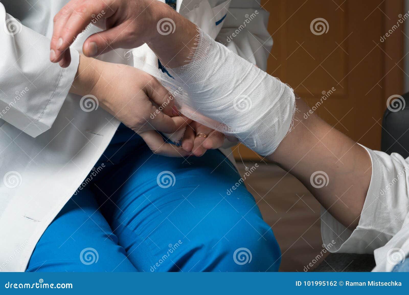 Um doutor fêmea enfaixa o braço paciente do ` s em sua casa