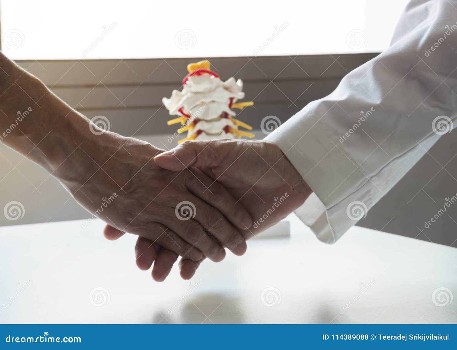 Um doutor que agita a mão um paciente
