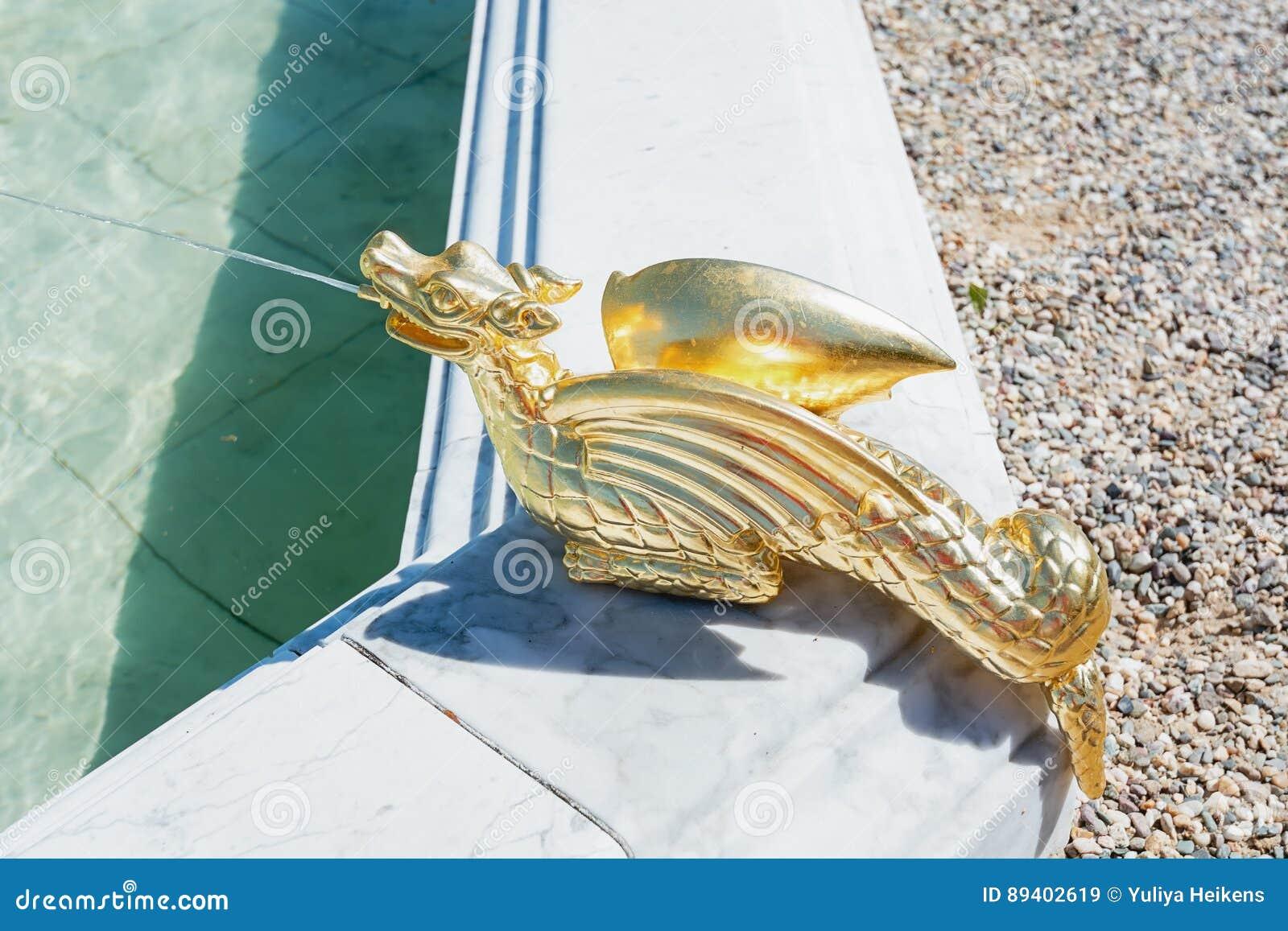 Um dragão dourado do esguicho da água como a decoração da fonte