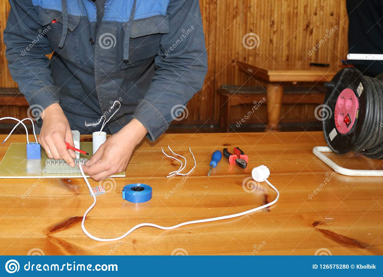 Um eletricista do homem que trabalha trabalhos, recolhe o circuito bonde de uma grande lâmpada de rua branca com fios, um relé em