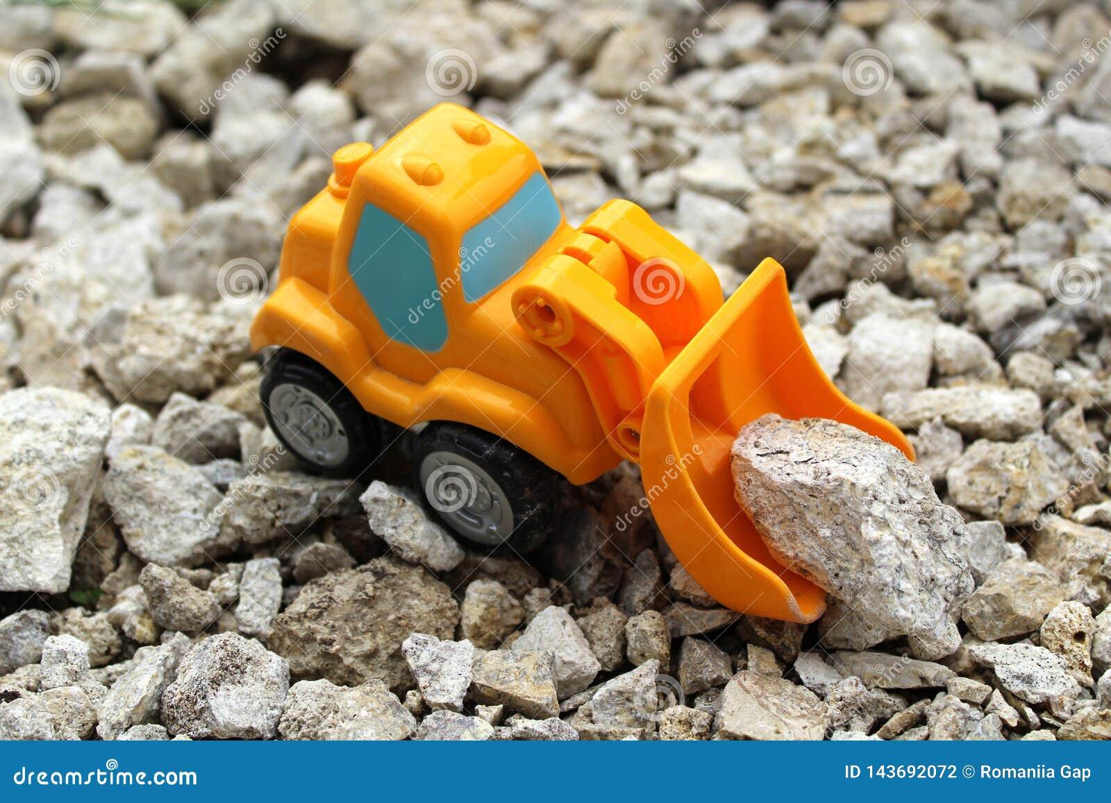 Um escavador alaranjado pequeno do brinquedo pegara pedras cinzentas