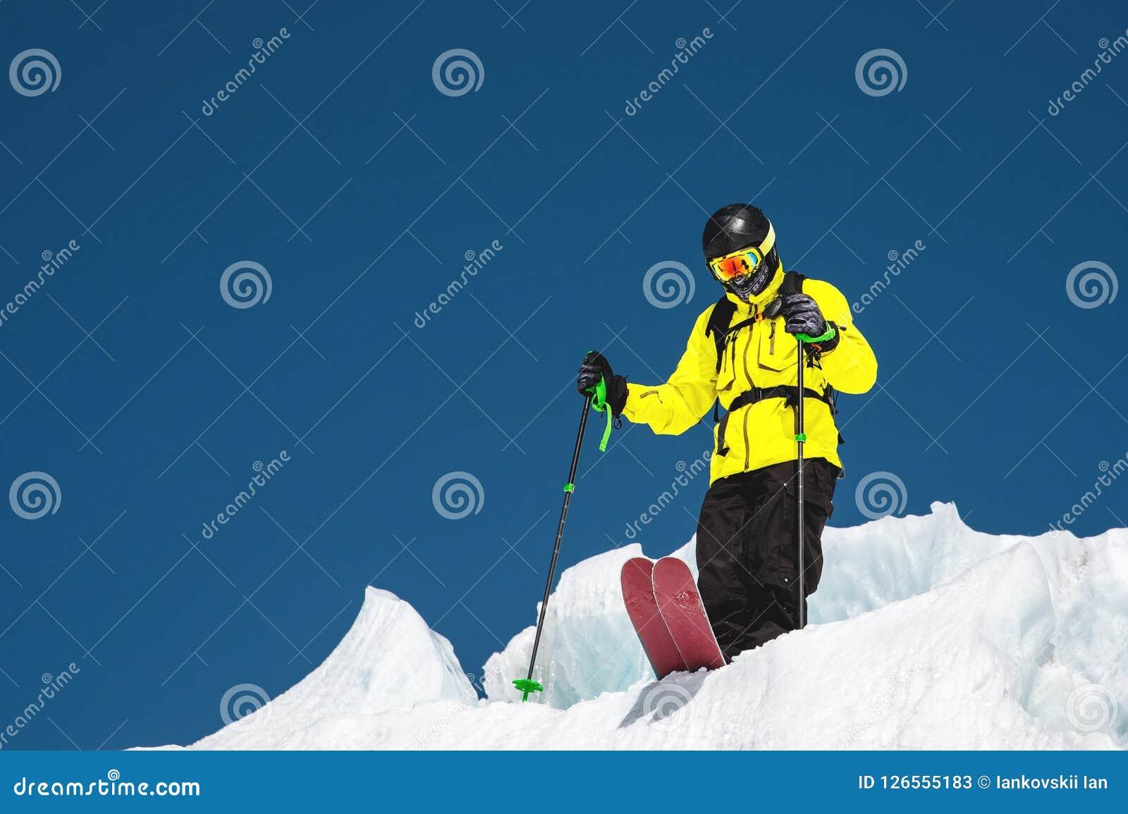 Um esquiador freerider no equipamento completo está em uma geleira no Cáucaso norte Esquiador que prepara-se antes de saltar do