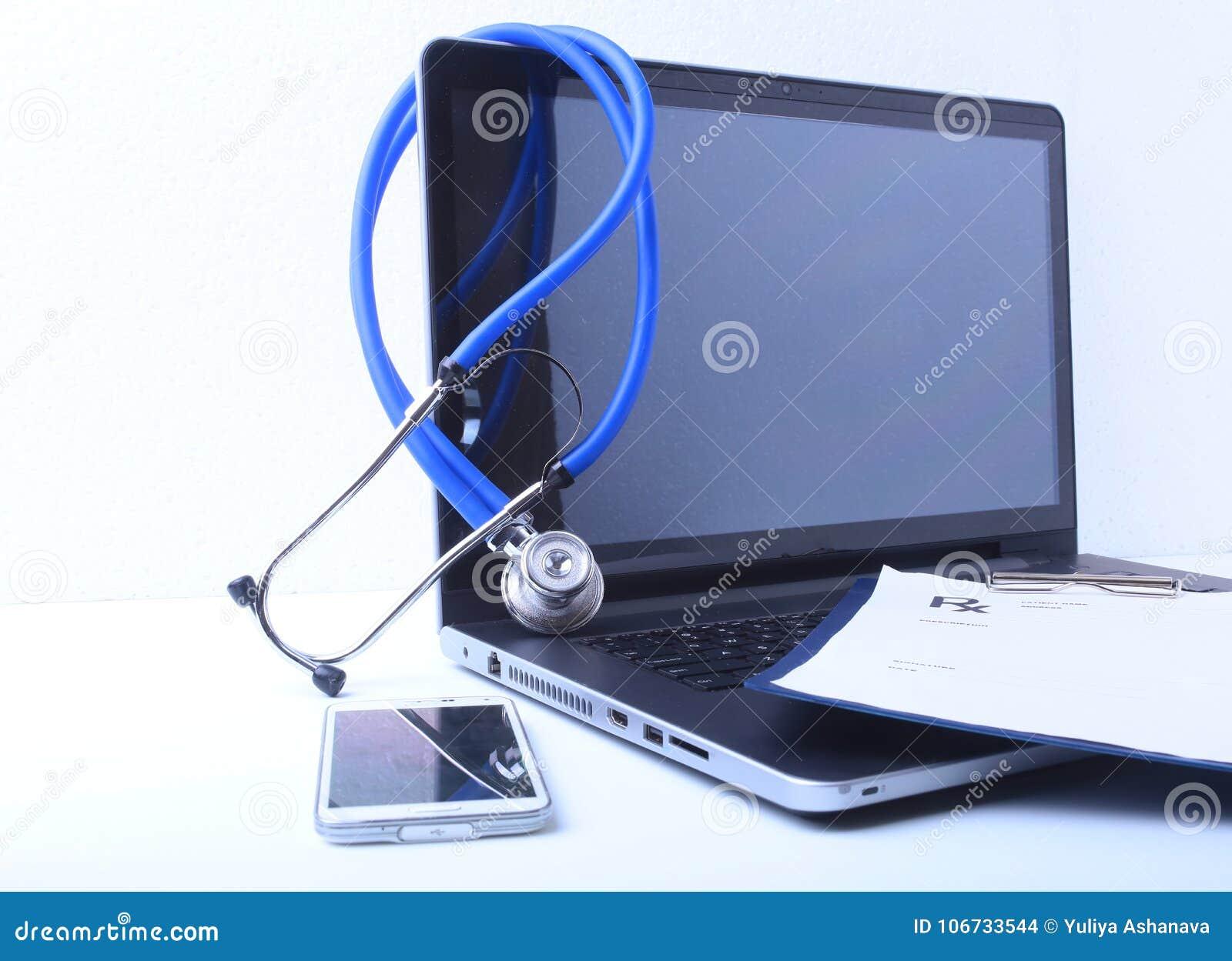 Um estetoscópio médico perto de um portátil em uma tabela de madeira, no branco
