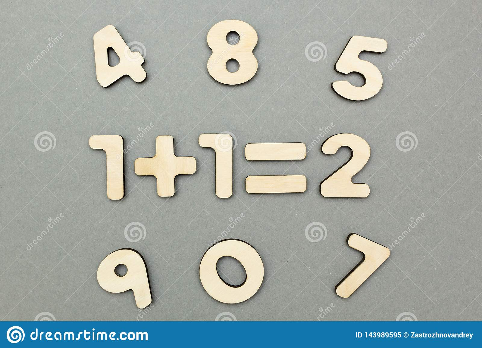 Um exemplo de figuras de madeira: um mais um é dois em um fundo cinzento do fundo