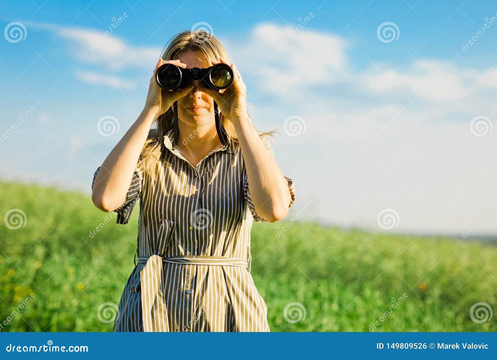 Um explorador da mulher está usando os binóculos pretos - exteriores
