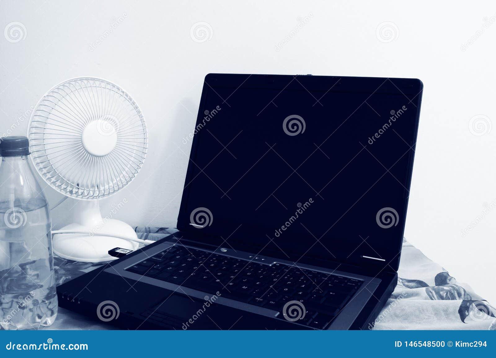 Um fã de tabela está ao lado de um portátil e de uma garrafa plástica enchidos com água