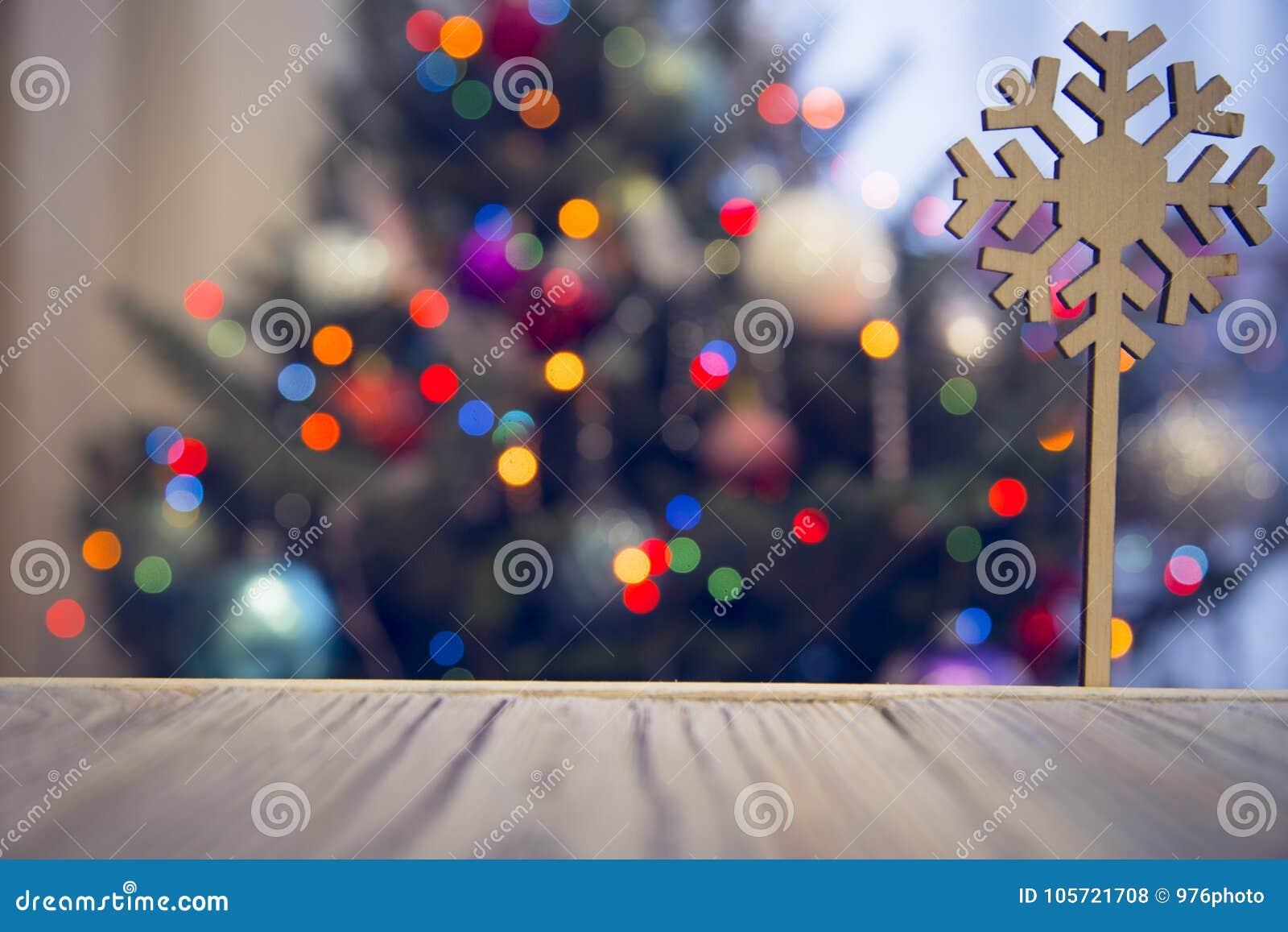 Um floco de neve de madeira em uma tabela de madeira contra a árvore de Natal decorada