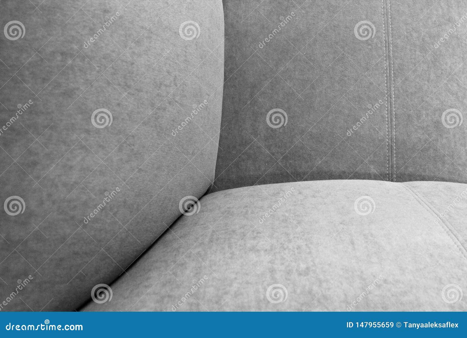 Um fragmento do assento, da parte traseira e do braço da poltrona cinzenta da veludinha