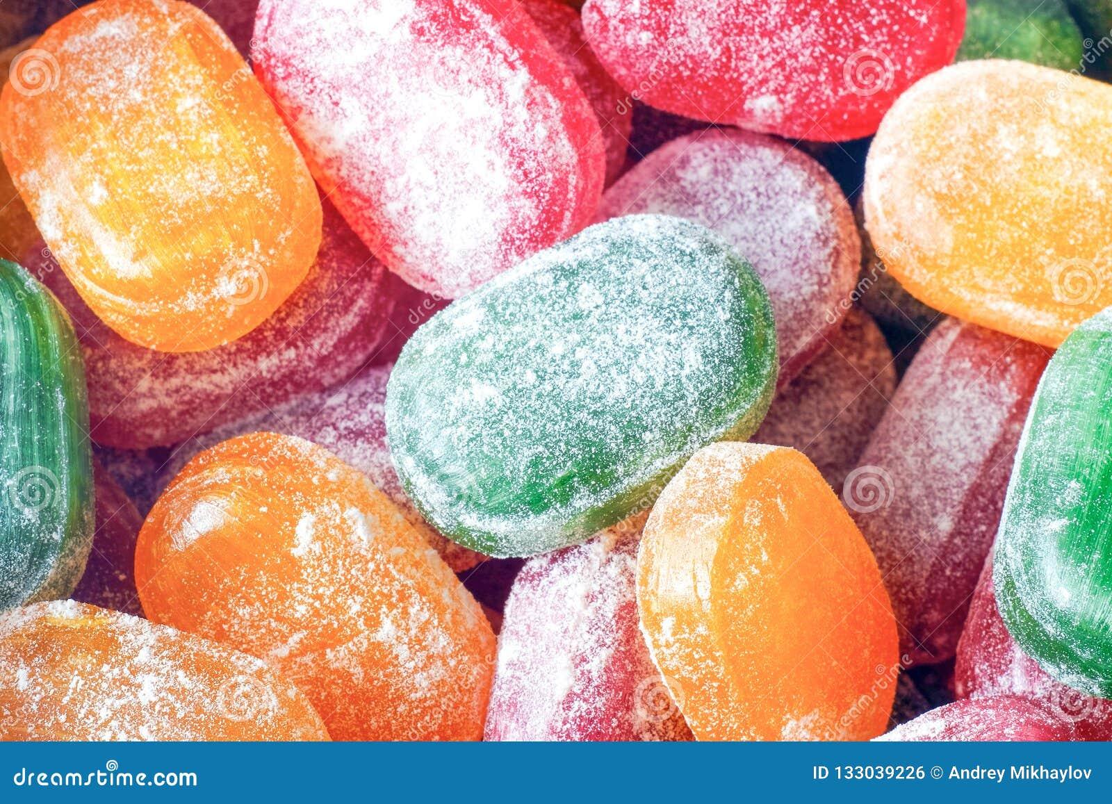 Um frasco de doces brilhantes A alegria das crianças, muitos doces Cores sortidos dos doces Caramelo no açúcar pulverizado