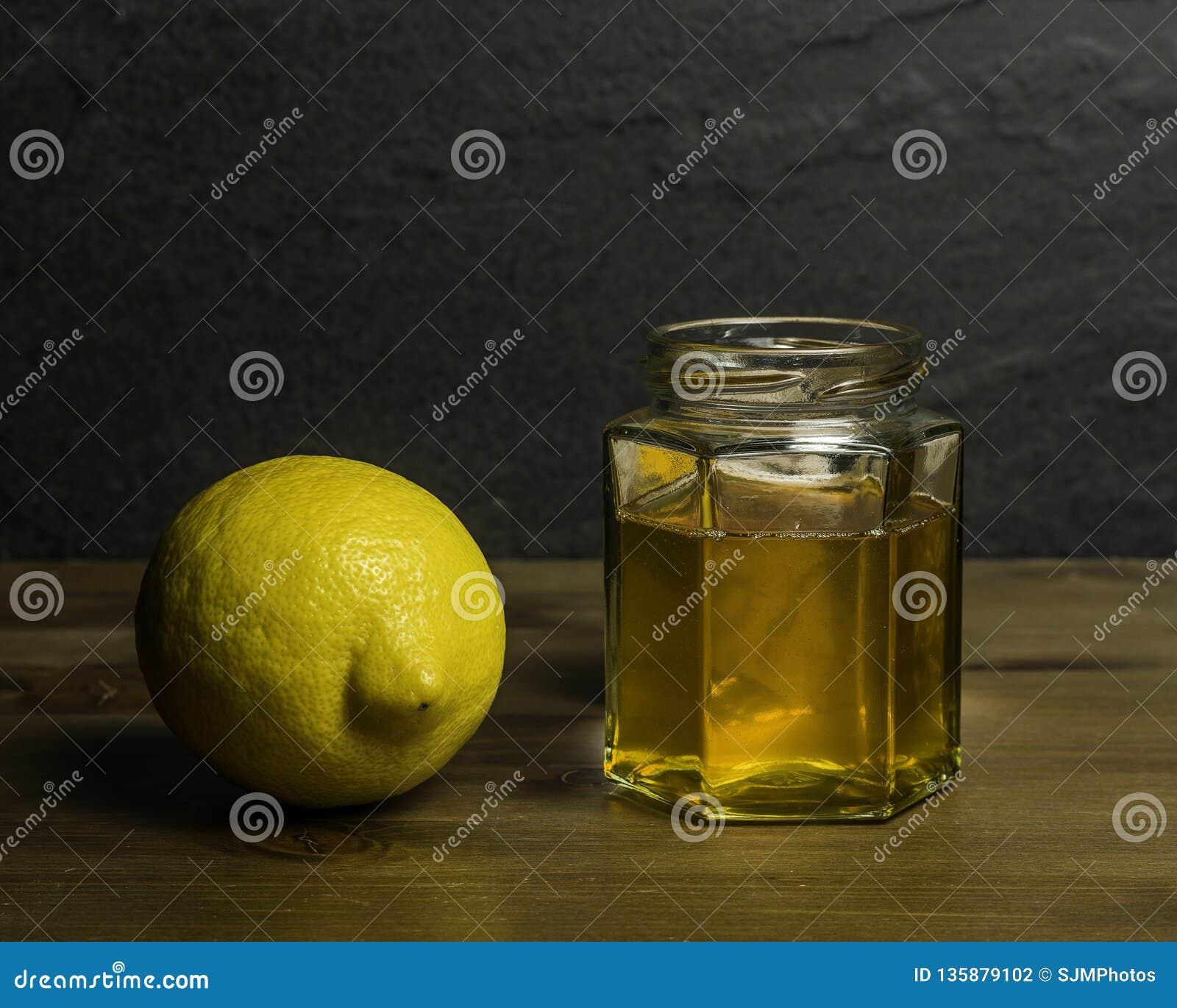 Um frasco do mel caseiro e do remédio frio do limão