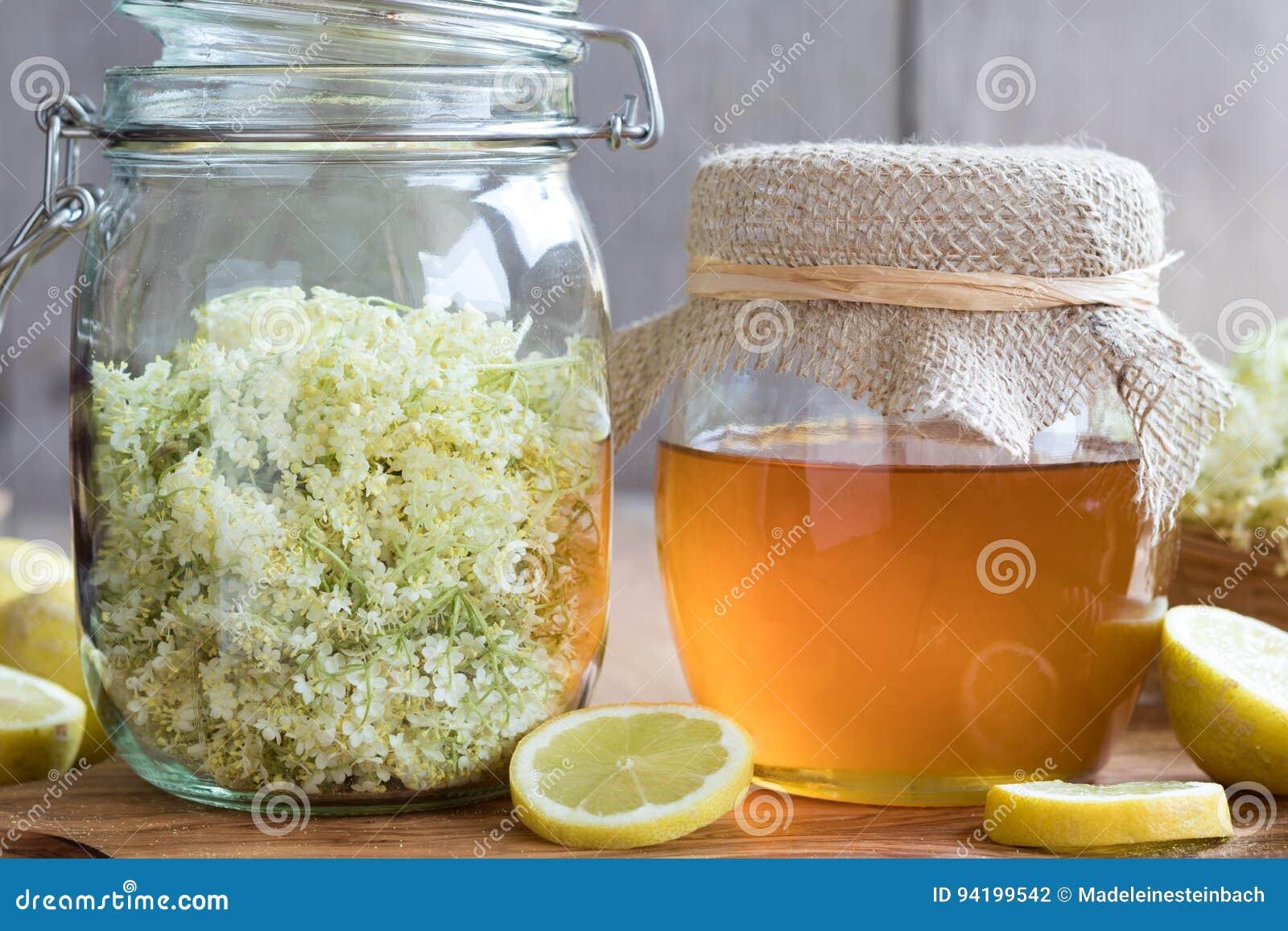 Um frasco do mel e da pessoa idosa floresce, apronta-se para fazer um xarope