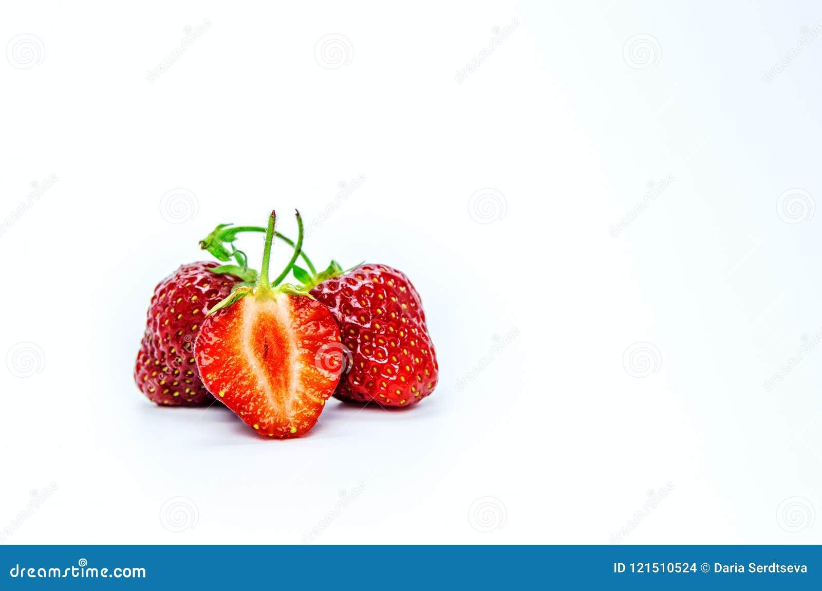 Um fruto do dragão em um corte e corte em fatias em um fundo branco Duas bagas inteiras das morangos e de uma baga do corte no fo
