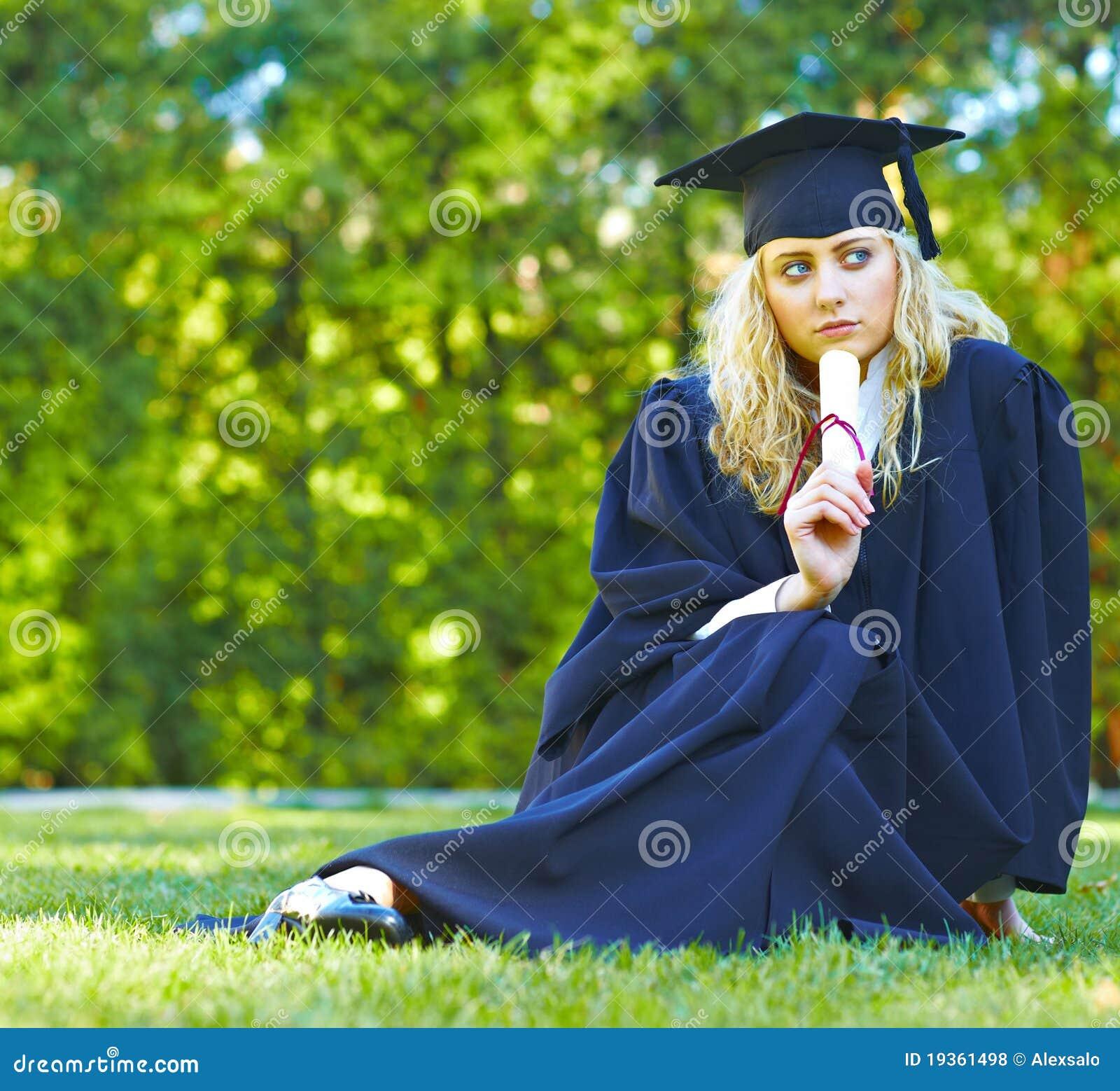 Um graduado bonito que senta-se no gramado