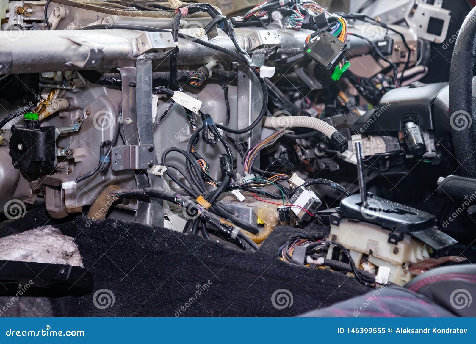 Um grande emaranhado de embaraça fios coloridos da fiação do carro encontra-se na cabine do carro desmontado com conectores e tom