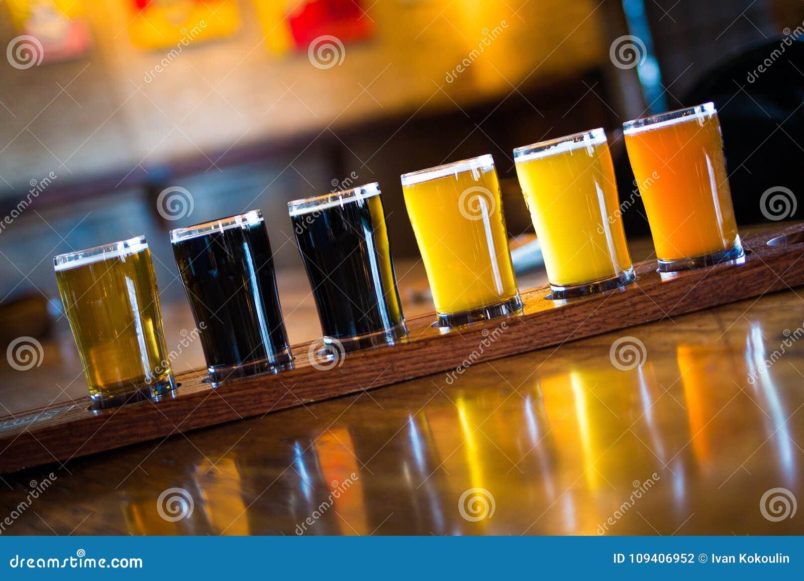 Um grupo da variedade de luz e de obscuridade das cervejas do ofício