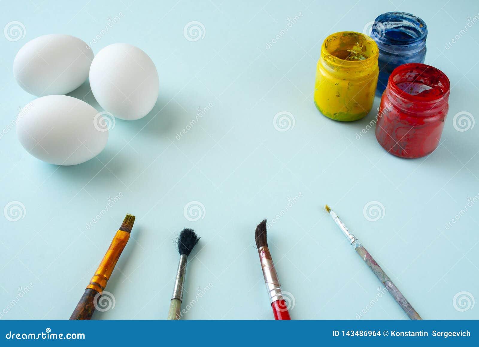 Um grupo das pinturas limpas brancas dos ovos, as azuis, as amarelas e as vermelhas e das escovas no fundo brilhante