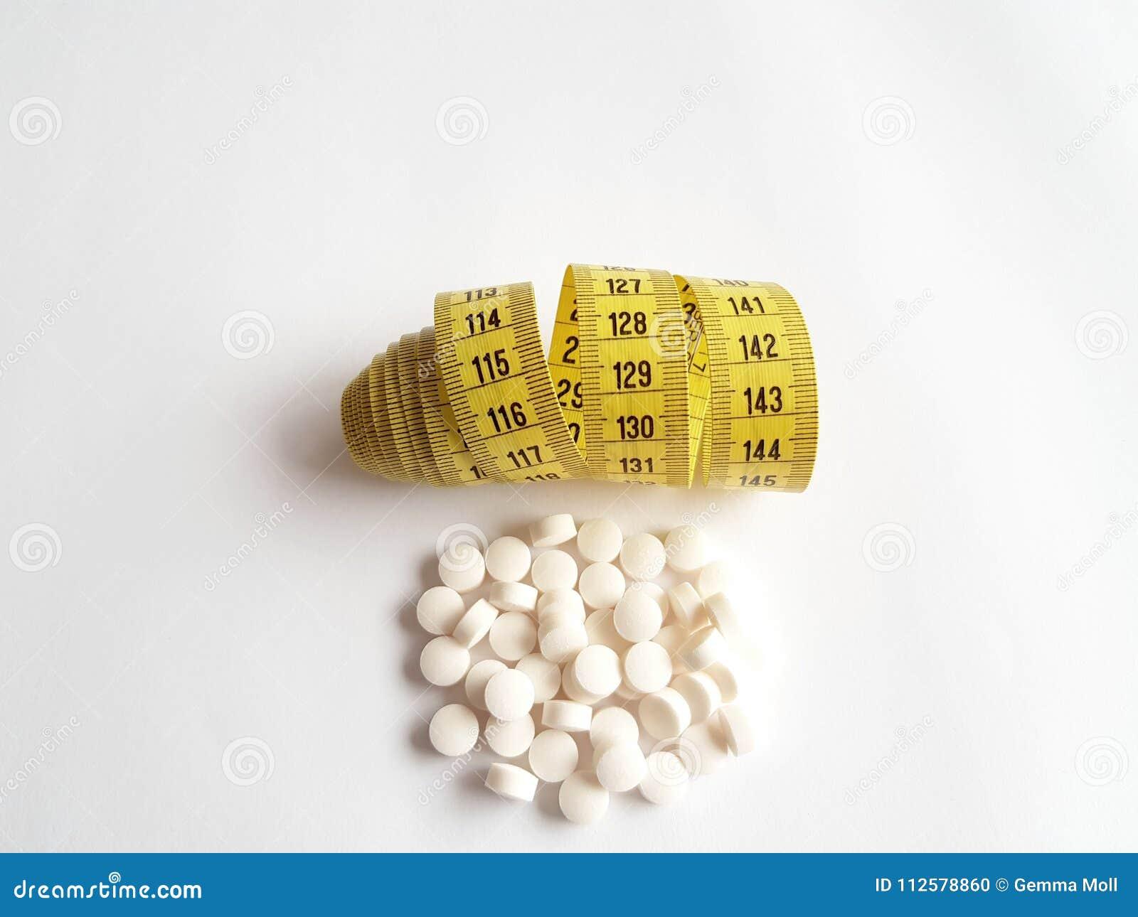 Um grupo de comprimidos ao lado de uma fita de medição