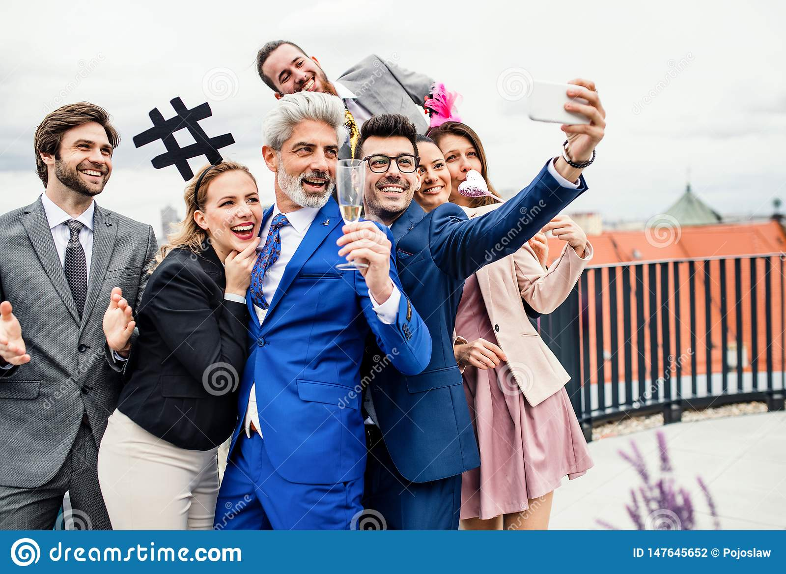 Um grupo de empresários alegres fora no terraço do telhado na cidade, tomando o selfie no partido