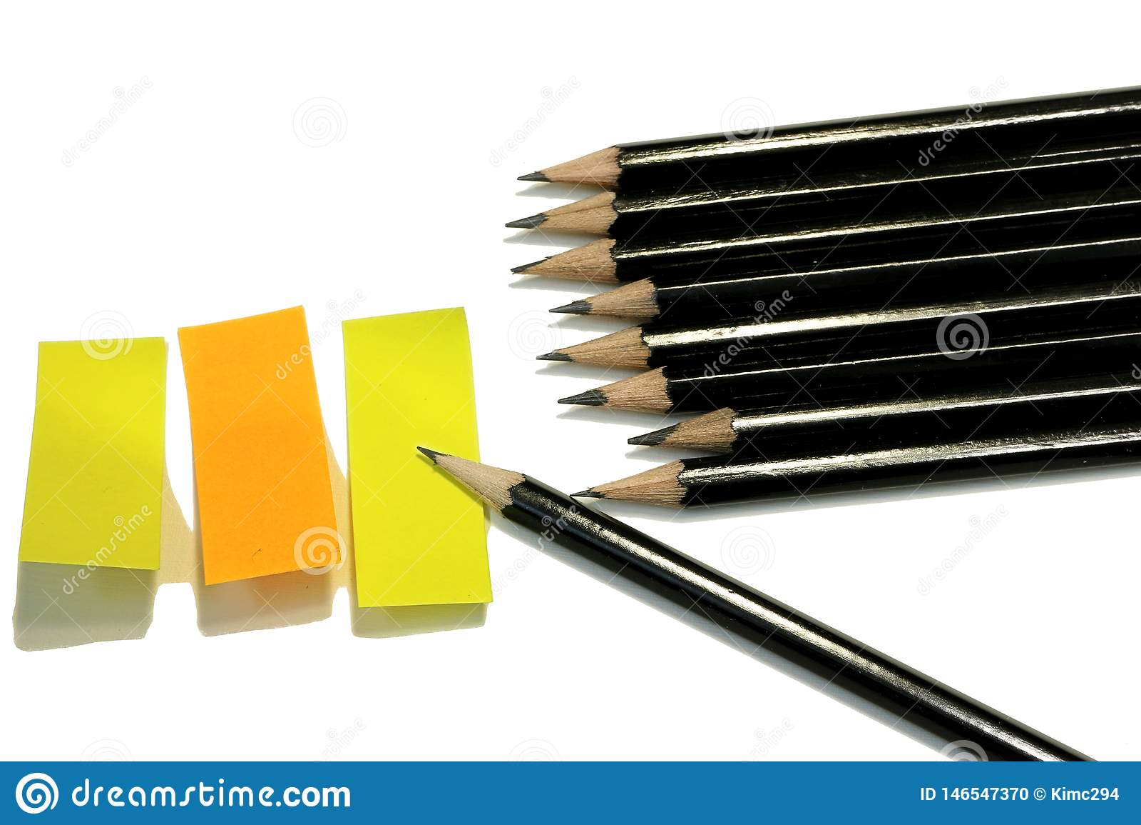 Um grupo de esboçar lápis e três notas pegajosas em amarelo e em alaranjado