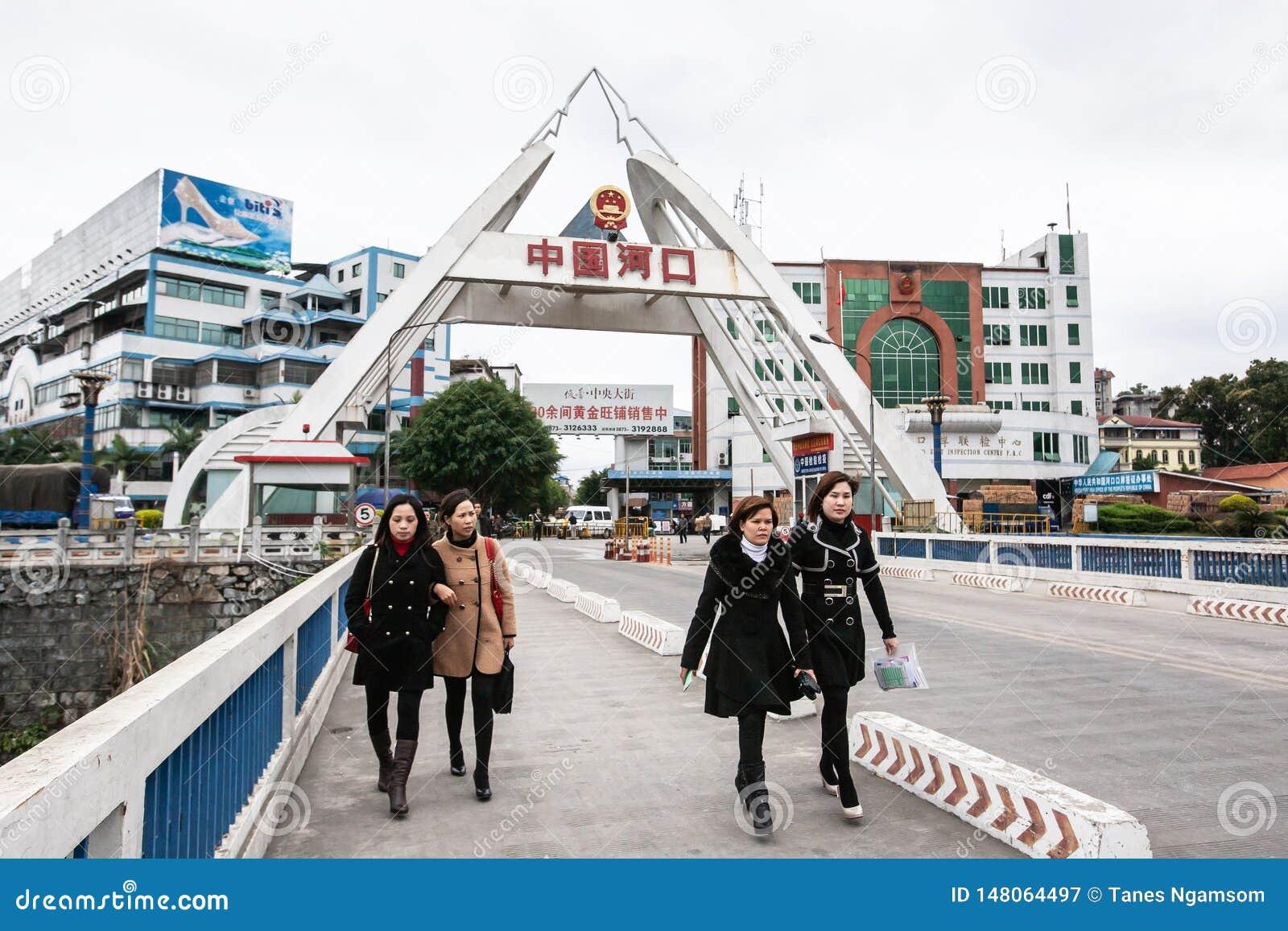 Um grupo de mulheres asi?ticas nos revestimentos longos que cruzam-se sobre a ponte sobre o Red River de Hekou, fundo de China a