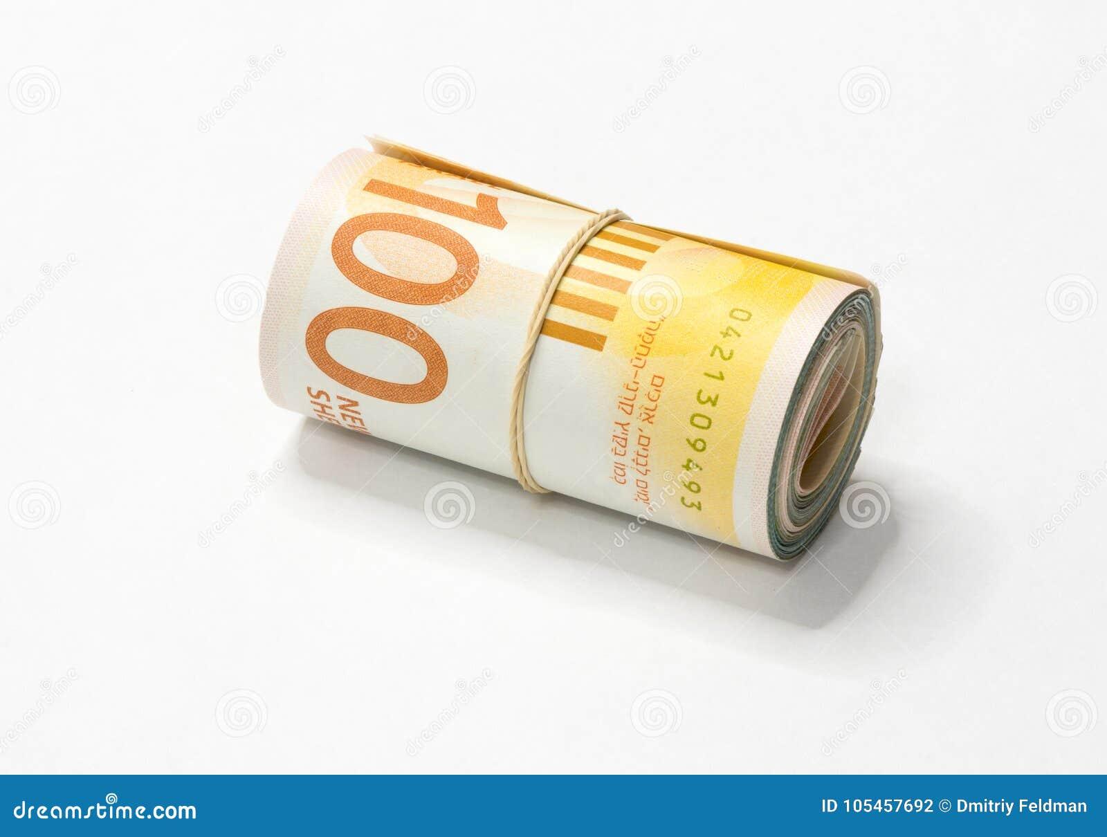 Um grupo de notas novas israelitas do dinheiro do NIS dos shekels rolou acima e mantido unido com um elástico simples em um backg