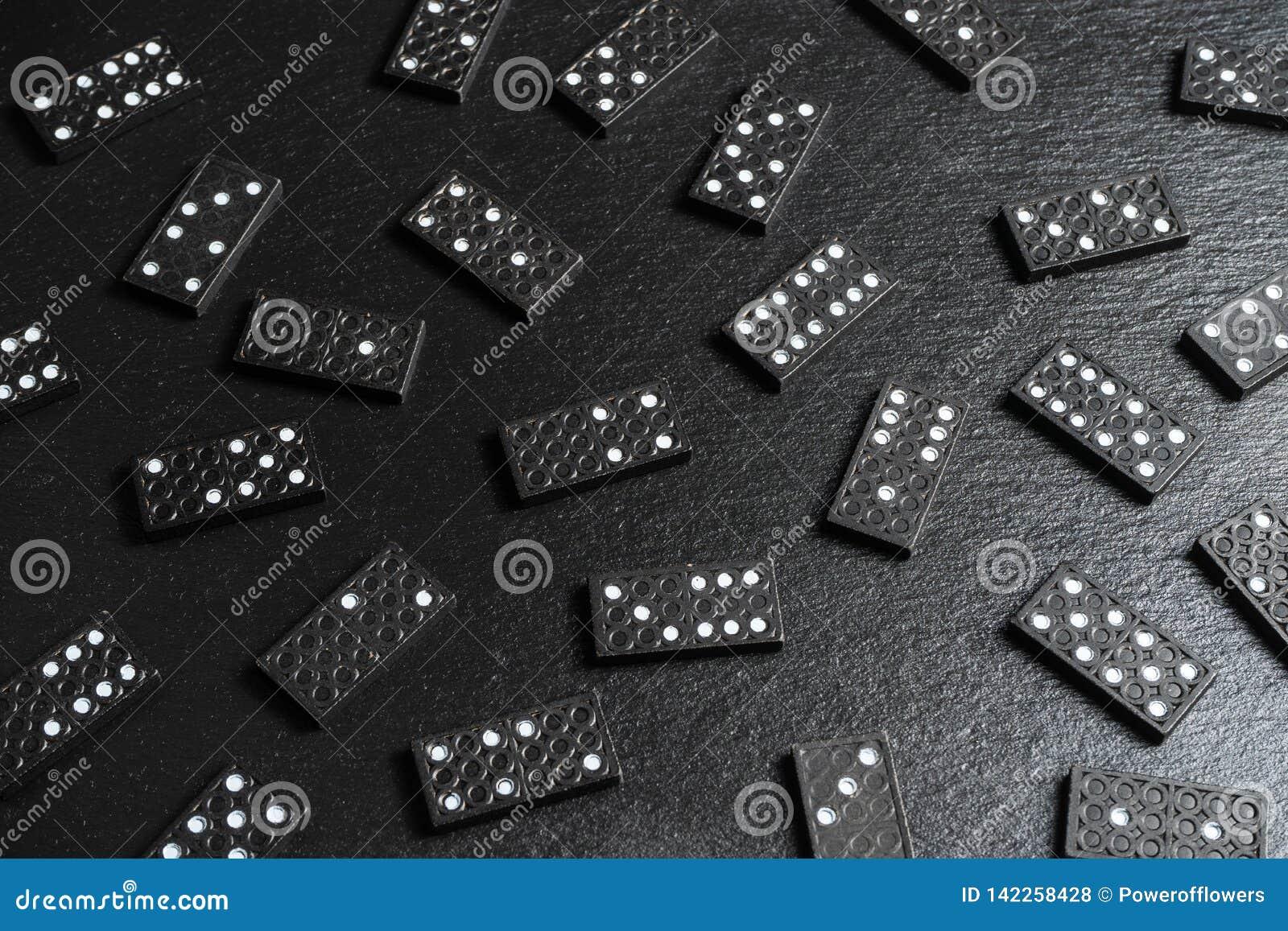 Um grupo de ossos do dominó no fundo de pedra preto