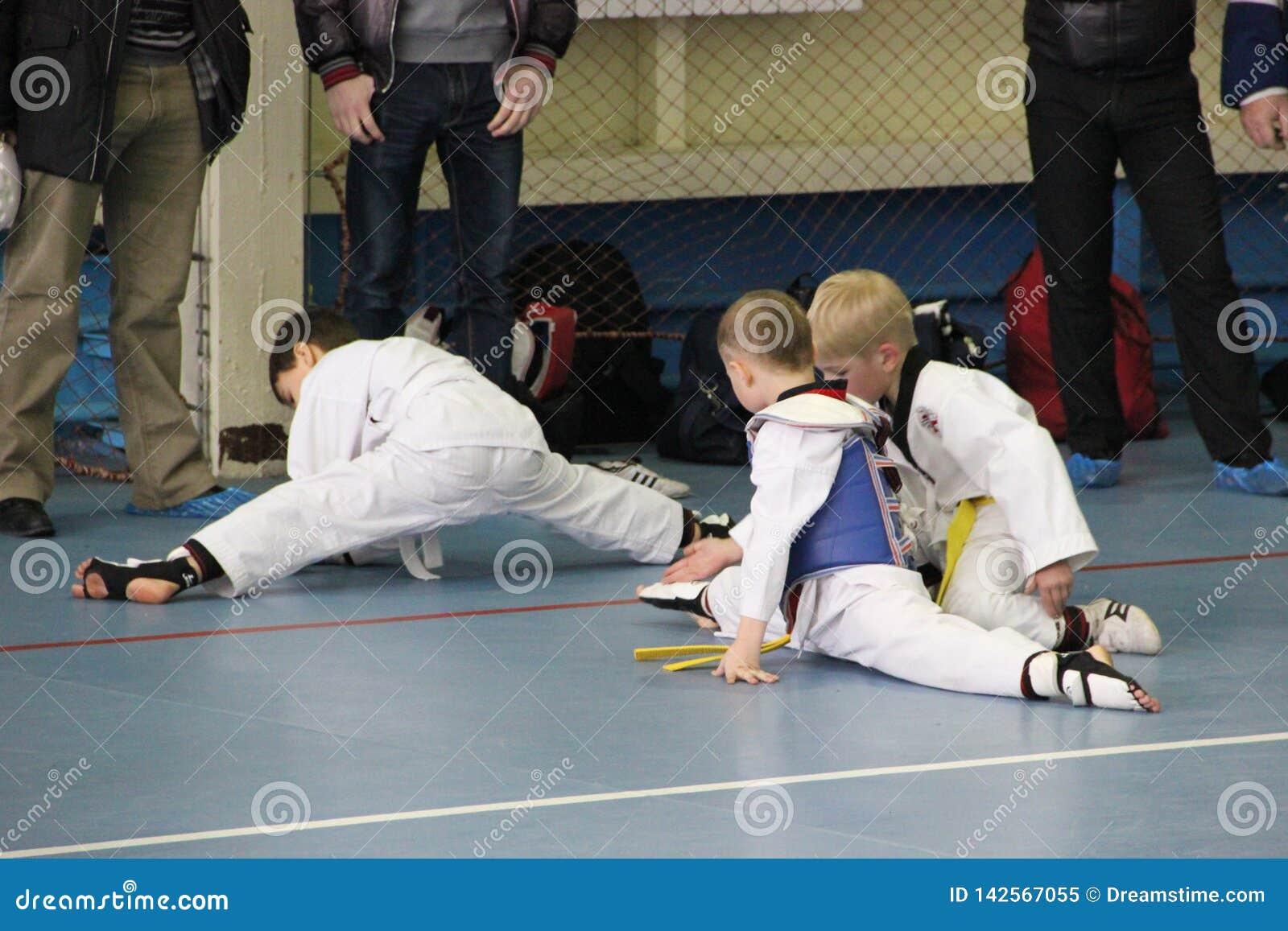 Um grupo de taekwondo que senta-se no assoalho para um resto