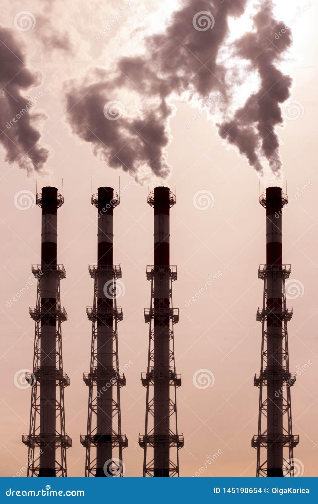 Um grupo de tubulações libera o vapor escuro do vapor do fumo poluição ambiental, poluição do ar por emanações tóxicas