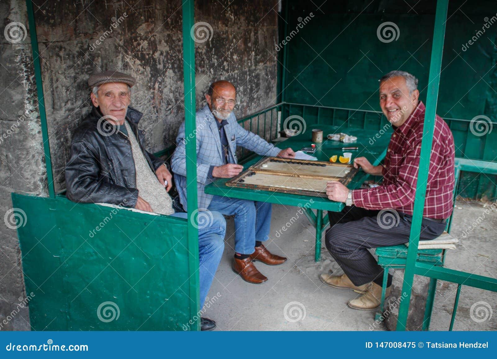 Um grupo de uns homens mais idosos está relaxando jogando a gamão