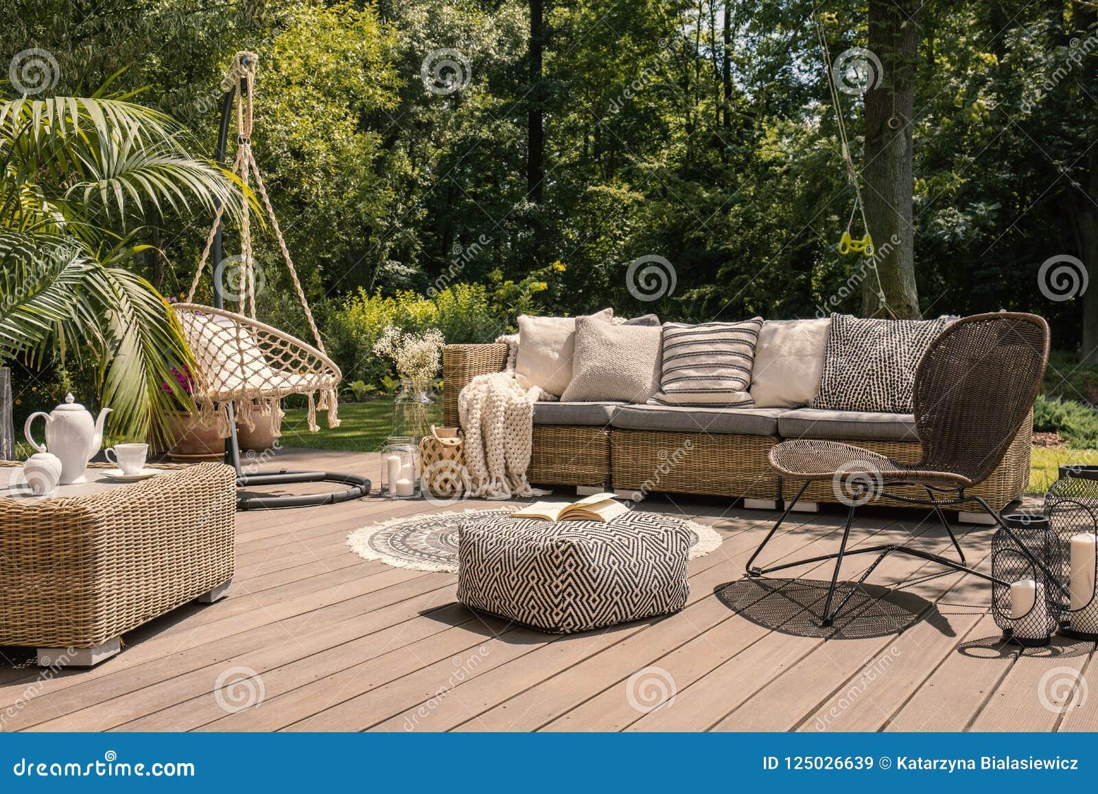 Um grupo do pátio do rattan que inclui um sofá, uma tabela e uma cadeira em um wo