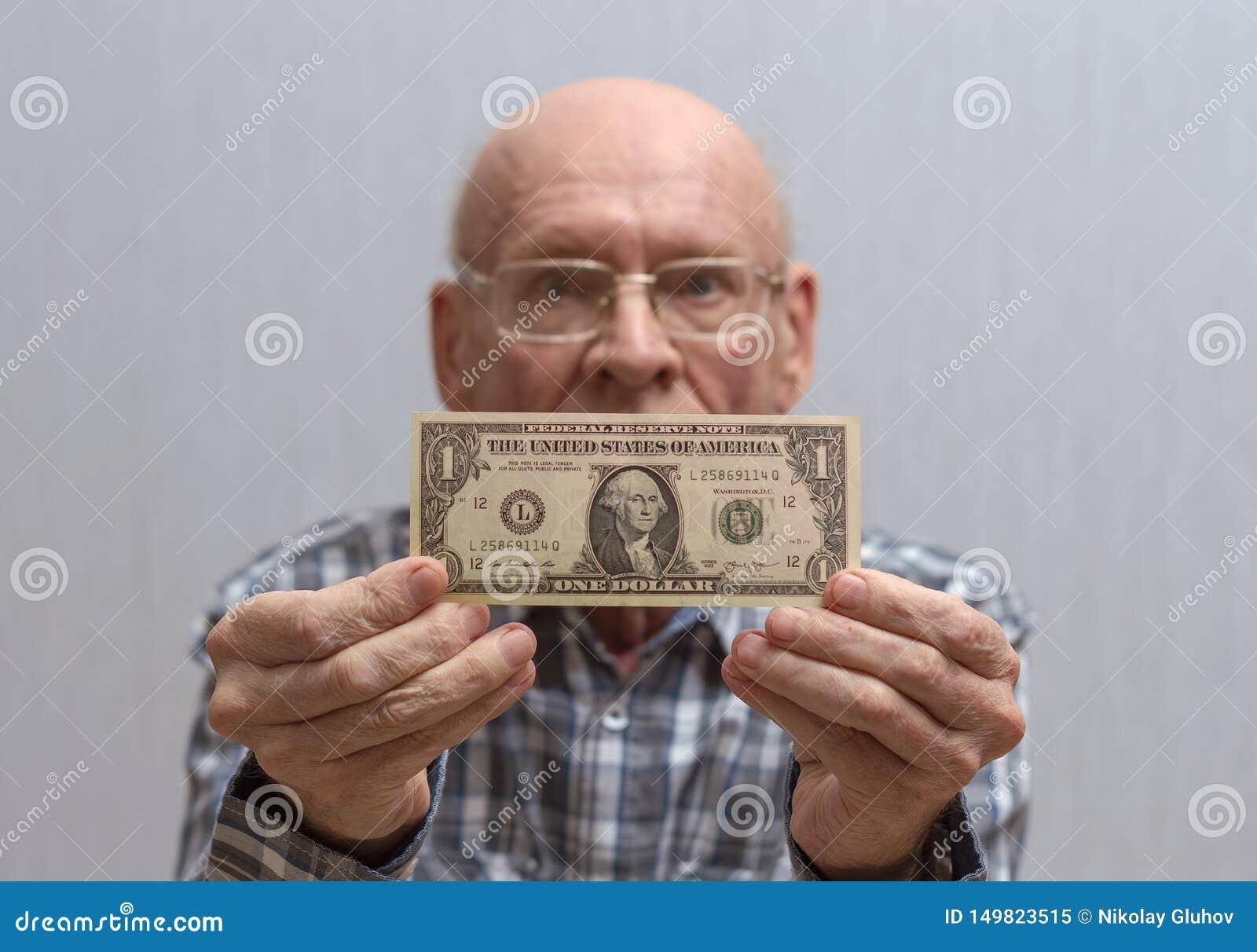 Um homem calvo idoso com vidros guarda uma c?dula na frente dele - um d?lar americano