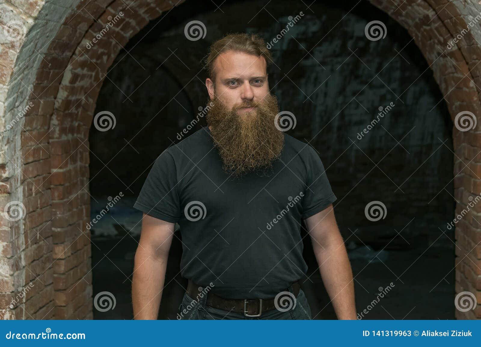 Um homem com uma barba, contra um arco do tijolo