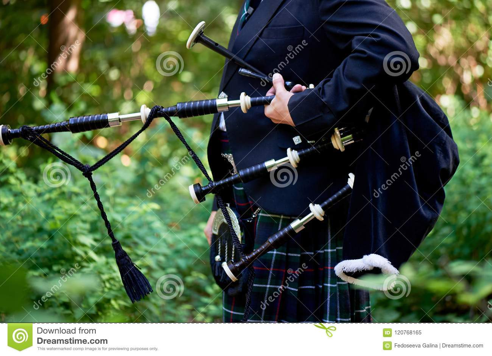 Um homem com uma gaita de fole, um kilt em uma gaiola com uma listra verde e vermelha cultura Os detalhes da saia do kilt e