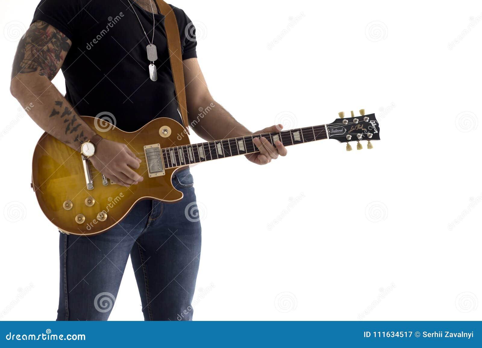 Um homem com uma guitarra elétrica que inclina-se contra uma parede do cimento feliz e relaxado esperando a mostra